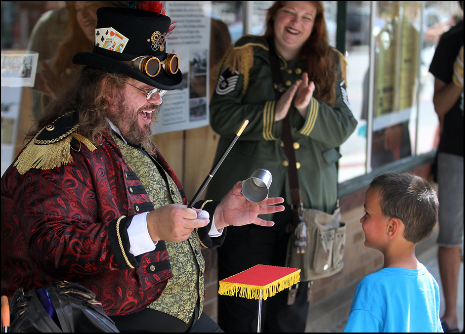 "In character as ""Dr. Robere DeGraf,"" Mark Pettey, left, of Naples, Fla., entertains six-year-old Brayden Genenbacher, of Hannibal, Mo., with a magic trick during the inaugural Big River Steampunk Festival Saturday Aug. 30, 2014, in the downtown Hannibal historic district. Pettey and numerous other costumed characters were in town for the festival. Steampunk enthusiasts embrace a genre of science fiction that marries steam-powered machinery and accoutrements with Victorian era or ""Wild West"" frontier style dress. (H-W Photo/Phil Carlson)"